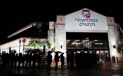 A Photo Relentless Church at Night With a String of Worshipers Going Inside
