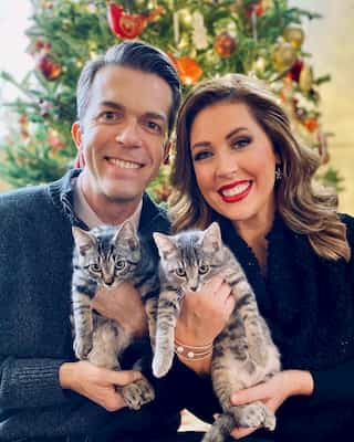 A photo of Alicia Smith and her husband Erik Karell, both holding their cats, Max and Mischa