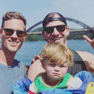 A photo of Christopher Landon (left) and his husband Cody Morris (right) and their son Beau (center)